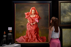 """© Licensed to London News Pictures. 27/06/2017. London, UK.  A woman views """"Red Paper Bride"""" by Zeng Chauanxing at The Arts & Antiques Fair taking place at Olympia in Kensington.  The event is the UK's largest and most established art and antiques fair and runs until 2 July. Photo credit : Stephen Chung/LNP"""