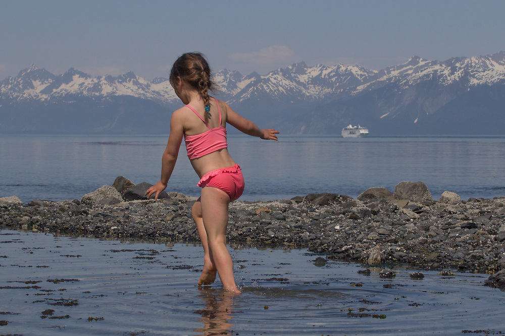 A young girl has fun exploring a tide pool in Glacier Bay with a cruise ship in the background. MR