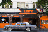 Slabtown bar, with a car sitting outside it