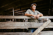 Portrait of a farmer resting on a fence.<br />