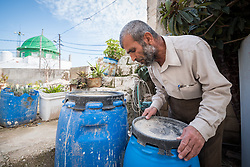 16 February 2020, Irbid, Jordan: Mahmoud Al-Omari opens a barrel in his garden in Al-Mazar. The barrels are used to keep rain water collected via drain pipes in times of the year when there is no water in the houses taps. Mahmoud is one of many beneficiaries to recently have received support from the LWF in setting up home-based farming in the area of Al-Mazar. By providing tools and seeds, the project has helped 150 families grow food for themselves and, in some cases, also earn an income from selling their surplus at local markets.