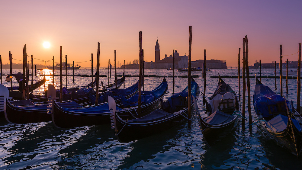 gondolas line the bank at st mark's square in venice at sunrise
