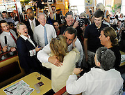 New Jersey Gov. Chris Christie center, kisses Paula Murray of Norwalk as Republican gubernatorial candidate Tom Foley, back center, and Mary Ann Springall, friend of Murray, looks on, during a visit to a diner, Monday, July 21, 2014 in Greenwich, Conn. (AP Photo/Jessica Hill)