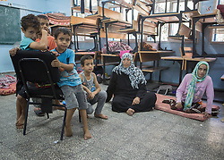 """© Licensed to Alison Baskerville. 14/07/2014. Gaza.   Naimah Abu Halima (56) sits with her daughter Hannah (32) in a UN school after fleeing from the north of Gaza following a warning from the Israeli Defence Forces (IDF).   Over 600 people have evacuated their homes and taken refuge in the school.  Hannah is disabled and cannot feed or wash herself and her mother must continue to care for her in the temporary shelter.   With no sign of the crisis ending the school is now concerned that they will run out of water and supplies.  """"I don't know how much longer we will be able to go on in this situation.""""  Commented Abdil Sawan, the UN representative within the school.  Photo credit : Alison Baskerville/LNP"""