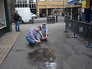 Men photographing puddle with smartphone camera, Near Leicester Sq. London. September 2016