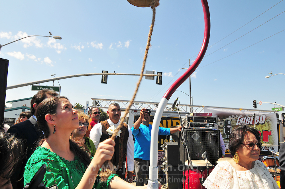 "Martha Gutierrez of the Mexican Consulate in San Jose rings Hidalgo's bell at Sunday's ""El Grito"" celebration in Salinas marking September 16th's anniversary of Mexico's independence from Spain. The annual fiesta, which occupies East Alisal Street between Wood and Sanborn, brimmed as usual with booths selling patriotic souvenirs and all manner of food and drink. Local businesses and nonprofits manned booths with information about health and community programs, while traditional ""bandas"" filled the afternoon with dance music and good cheer."