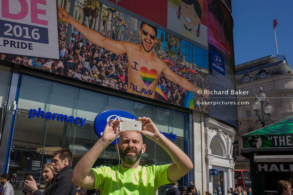 A man in fluorescent yellow stops to take a picture with a smarphone in Piccadilly Circus.