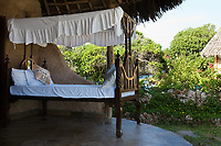 old style bed on a open patio of a room in tropical nature