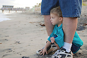 A small boy hides behind his dad as he watches the waves break on the beach on a windy afternoon in Lake Worth, Florida.