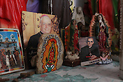 Religious altar at the La Puya resistance blockade displays images of the Virgin of Guadalupe, slain Salvadorian bishop Oscar Romero, and former Archbishop of Guatemala Rodolfo Quezada Toruño, a staunch anti-mining promoter who passed away on June 4, 2012. Since March 2nd, 2012, local neighbors from San José del Golfo and San Pedro Ayampuc have blocked the entrance to the EXMINGUA gold mine - owned by Kappes, Cassiday & Assocaites (KCA) based in Reno, Nevada, USA. Residents from the communities claim the industrial activity in their territories as illegal since they were not appropriately consulted before the mine began operating. La Puya, San Pedro Ayampuc, Guatemala. May 14, 2013.
