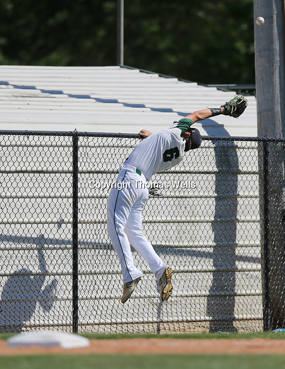 Mooreville third baseman Brent Cummins tries his best to come up a foul ball but the fence keeps him from making the catch.