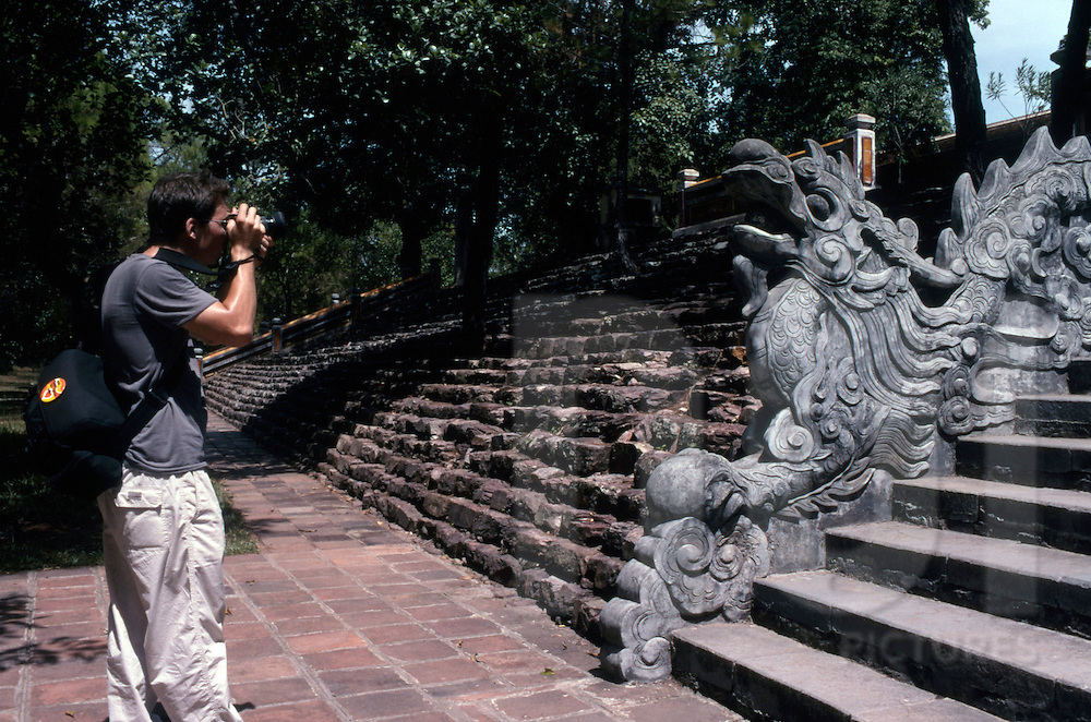 A tourist takes a picture of a dragon's sculpture in Hue's citadel
