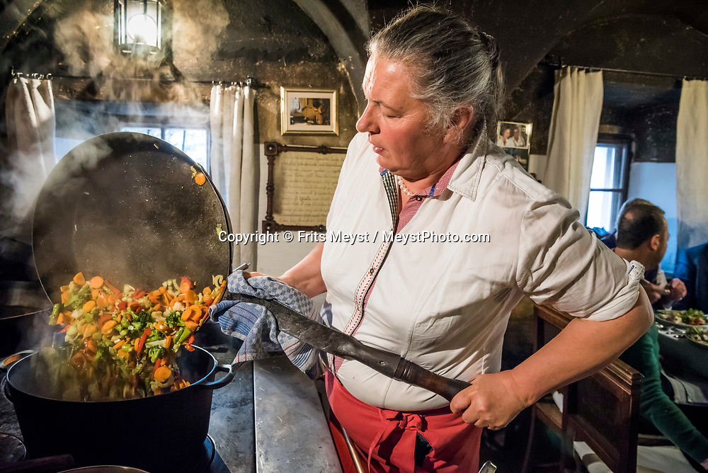 Stuhlfelden, National Park Hohe Tauern, Salzburgerland, Austria, April 2017. Theresia Bacher cooks Pinzgauer traditional food for guests on an open fire in the kitchen of her 500 year old farmhouse. The Schwaigerlehen farmhouse is richly decorated with old traditional furniture and serves as a bed and breakfast where guests can stay in one of the cosy historical rooms. Photo by Frits Meyst / MeystPhoto.com