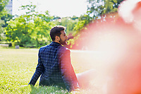 Rear view of young attractive businessman sitting on the grass during break