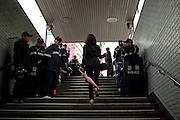 Frau mit einem rosa Regenschirm am Tag der Feierlichkeiten von Buddhas Geburtstag (2. Mai 2009) an einem von koreanischen Polizisten bewachten Ausgang der Metro in Seoul im Zentrum der koreanischen Metropole.<br /> <br /> Woman with a pink umbrella leaving an exit of the Seoul metro protected by police man on the day of Buddhas birthday (2nd of May 2009) in the center of the Korean metropolis Seoul.