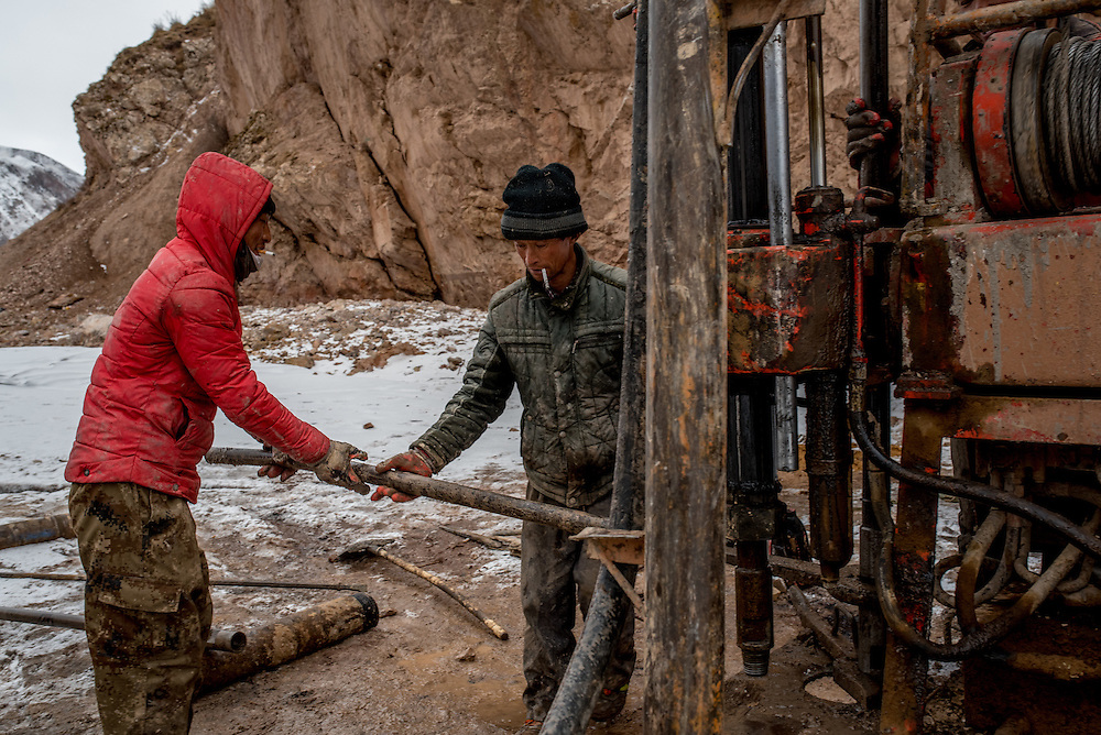 Workers remove a piece of tubing from their machinery while taking soil samples on the frozen Mekong river. The team is taking earth samples from the river bed in preparation for the construction of a new bridge over the Mekong in Zado, Tibet (Qinghai, China).