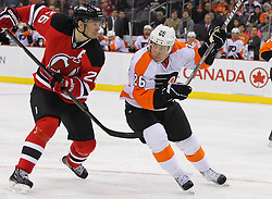 Jan 21; Newark, NJ, USA; Philadelphia Flyers defenseman Erik Gustafsson (26) hits New Jersey Devils center Patrik Elias (26) during the third period at the Prudential Center. The Flyers defeated the Devils 4-1.