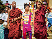 28 OCTOBER 2015 - KYAUKTAN, MYANMAR:  Burmese novices (young, not yet fully ordained monks) and a friend wait to the catch a ferry to take them to Kyaik Hmaw Wun Pagoda, a pagoda on an island about two hours from Yangon during the  Thadingyut festival. The Thadingyut Festival, the Lighting Festival of Myanmar, is held on the full moon day of the Burmese Lunar month of Thadingyut. As a custom, it is held at the end of the Buddhist lent (Vassa). The Thadingyut festival is the celebration to welcome the Buddha's descent from heaven.   PHOTO BY JACK KURTZ
