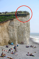 ** Red circle indicated the point where members of the public were standing next tot he cliff edge**<br /> © Licensed to London News Pictures. 22/04/2019. Birling Gap, UK.  Reckless members of the public risk their lives on the edge of the crumbling chalk cliffs of the Seven Sisters near Eastbourne, UK. The iconic sheer white cliffs are up to 400 feet high and have had recent record cliff falls due to erosion, but many people, some even holding children, cannot resist the temptation to peer over the edge to get photos. Some people are even seen jumping in the air just feet from the edge.  Photo credit: Peter Cripps/LNP
