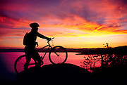 Mountain biker Monique Sady pauses on the Great Flume trail above the east shore of Lake Tahoe to watch a spectacular sunset. The flume trail is less than an hour from Reno.