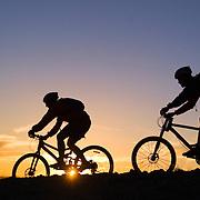 A photo of a couple Mountain Biking At Sunset