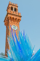 Beautiful mixture of old and new with a blue glass art sculpture set against an old brick tower in Murano, Venice, Italy.