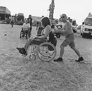 People being pushed in wheelchairs at a Rock and Blues festival
