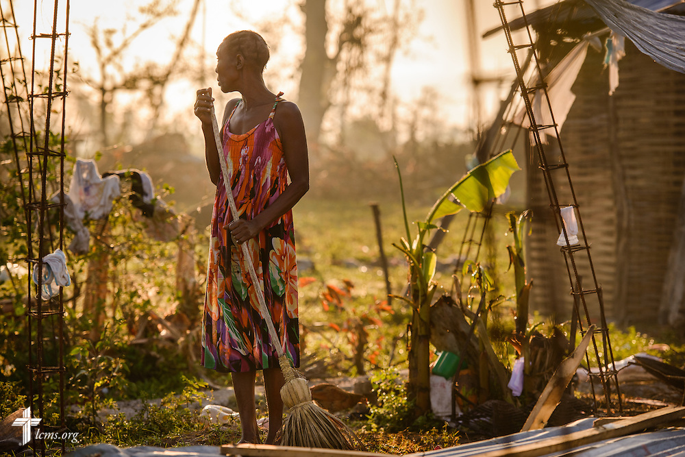 A woman sweeps the ground near the remnants of her home damaged by Hurricane Matthew on Wednesday, Oct. 12, 2016, in a rural area of Les Cayes, Haiti. LCMS Communications/Erik M. Lunsford