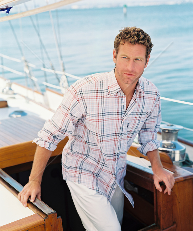 Goodlooking man coming up on deck on his yacht