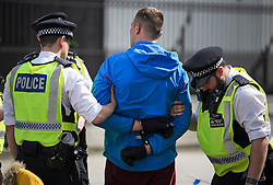 © Licensed to London News Pictures. 18/04/2019. London, UK. A man is placed in handcuffs following as altercation with protestors from Extinction Rebellion, as they occupy Parliament Square for a fourth day. Protesters are demanding urgent government action on climate change. Photo credit: Ben Cawthra/LNP