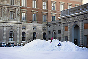Children play on a pile of snow outside The Royal Palace, Stockholm, Sweden in winter.