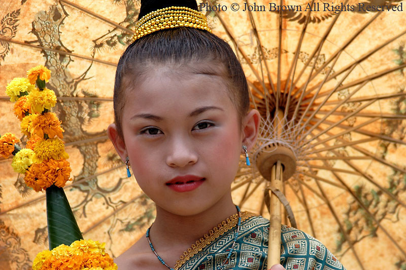 A young girl who is a participant in the annual Lao New Year (Bun Pi Mai) parade takes a moment to relax with her umbrella in Luang Prabang, Laos. The streets of Luang Prabang are lined with tourists and locals alike as they enjoy the colorful display of traditional Lao culture that is on display at this yearly event...
