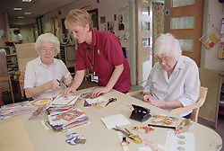 Clinic assistant showing two elderly women how to use scissors and a hole punch to make Christmas cards during occupational therapy session,