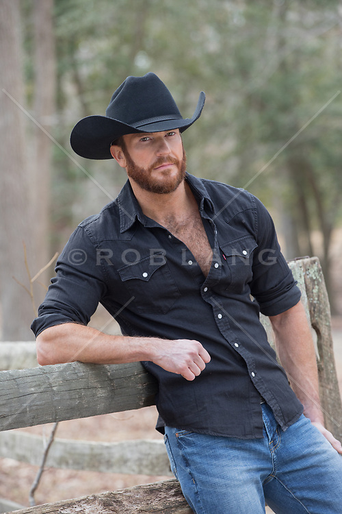 sexy bearded cowboy leaning on a spilt rail fence