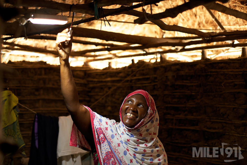 Fatuma, treasurer of the village energy committee, switches on her solar powered light in Chekeleni village, near Mtwara, Tanzania...
