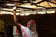 Fatuma, treasurer of the village energy committee, switches on her solar powered light in Chekeleni village, near Mtwara, Tanzania...