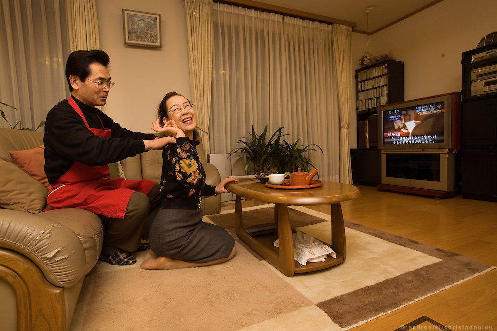 Hayashi Yoshitake (65) - reformed husband -  massaging his wife Takeko Yoshitake (65) while they are watching TV. They are both middle school teachers, she teaches music. They have been married for 39 years.  Tokyo 9 Feb. 2007
