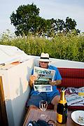 Holidaymaker reads Travel section of broadsheet newspaper on river cruiser, Norfolk Broads, UK