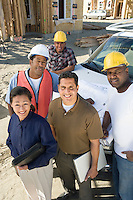 Architect and four construction workers standing in front of car on construction site