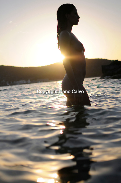 Young attractive woman relaxing at sunset, in the Mediterranean Sea waters