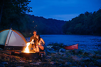 Millinial couple camping along side the James River in the Blue ridge Mountains of Virginia.