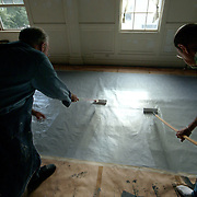 August 10, 2007 -- BRUNSWICK, Maine. Working artists Bev Bevilacqua, left, of Brunswick and Rod Cart of Phippsburg, prepare a sheet of Tyvek to be an outdoor mural by painting it with a latex primer. The mural, 32 feet long by 8 feet wide, will be called ?Dance of Two Cultures? and is designed by Hallowell artist Chris Cart. It will depict the exchange of culture between Brunswick and its sister city, Trinidad, Cuba and be worked on in the 3rd floor loft above Georgetown Pottery at 11 Pleasant St through March, 2008. The organization hopes that members of the community will contribute to the painting of the mural. For more information go to www.brunswicktrinidad.org .   Photo by Roger S. Duncan. .