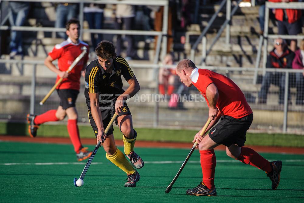Mo Gandhi of Beeston takes on Ryan Ravenscroft of Holcombe during their match in the England Hockey Men's Cup