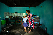 In the morning, Tara Dahal helps her daughter with her school uniform in the family kitchen. A biosand filter allows Tara to wash fruit and vegetables with uncontamintaed water, allowing her to be confident that her children are far less likely to become ill.