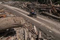 May 4, 2019 - Sigi, Central Sulawesi, Indonesia - Residents pass the road between wood piles due to flash floods in Tuva Village, Gumbasa Regency, Sigi Regency, Central Sulawesi Province, Indonesia, Saturday (May 4, 2019). The village was isolated because the road was cut off due to flash floods since Sunday (April 28, 2019) and could be crossed again after mud material and wood piles covering the road were successfully removed. The flash floods washed away 30 houses, piled up 500 settlements including houses of worship and schools and resulted in more than 2,500 residents being evacuated to safety. (Credit Image: © Basri Marzuki/NurPhoto via ZUMA Press)