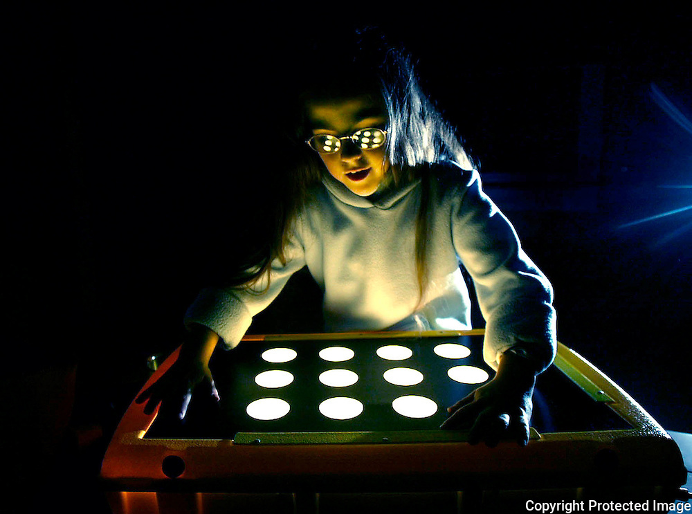 Annabelle Costanzo tries to see round shapes on a light table.  She was born blind, and hopes that a series of operations will allow her to see for the first time in her life.