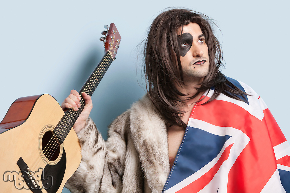 Young man with British flag holding guitar against light blue background