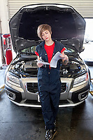 Young female mechanic reading paper with open bonnet of car in garage