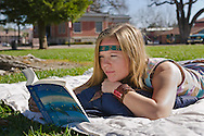 Young woman reading on grass at the City Park Plaza, Paso Robles, San Luis Obispo County, California