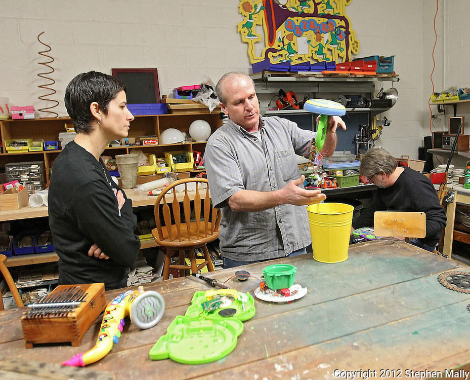 Mike Sanders (from right) explains to Kelly Kolln, both of Cedar Rapids, how they built a musical instrument out of various electronic parts at the Cedar Rapids Epicenter inside Cedar Valley Habitat for Humanity ReStore, 350 6th Ave SE in Cedar Rapids on Saturday, February 18, 2012. (Stephen Mally/Freelance)